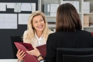 2 Frauen im Vorstellungsgespräch mit einer Bewerbungsmappe in der Hand